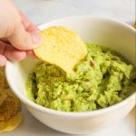 hand holding chip with scoop of guacamole