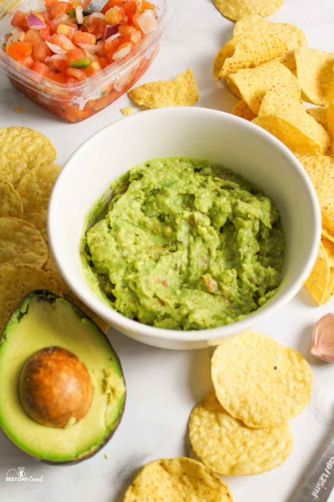 guacamole in a white bowl surrounded by chips and ingredients