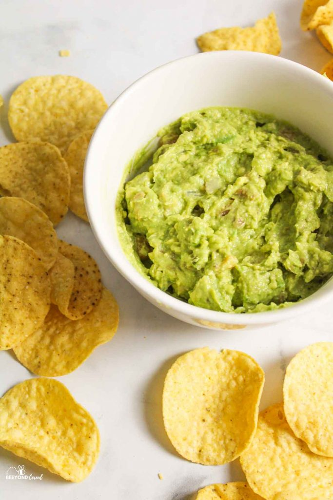 guacamole in a white bowl next to scattered chips