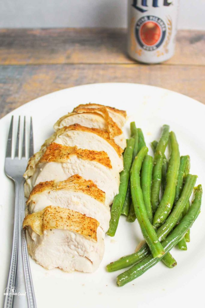 a fork, chicken breast and green beans on a plate with a can of beer in the background