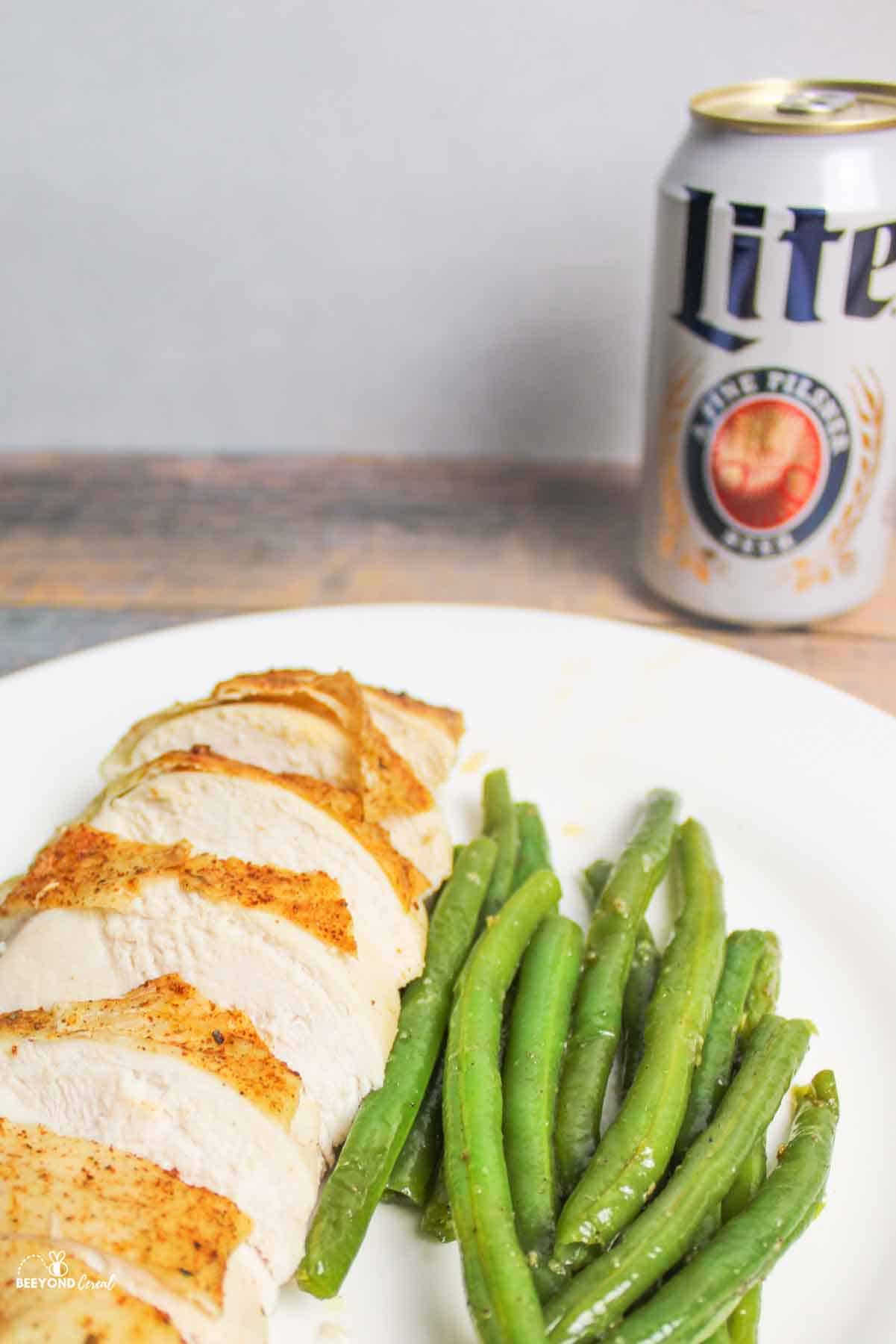 a sliced chicken breast and green beands on aplate with beer in the background