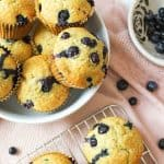 an opened blueberry muffin packed with blueberries in front of more