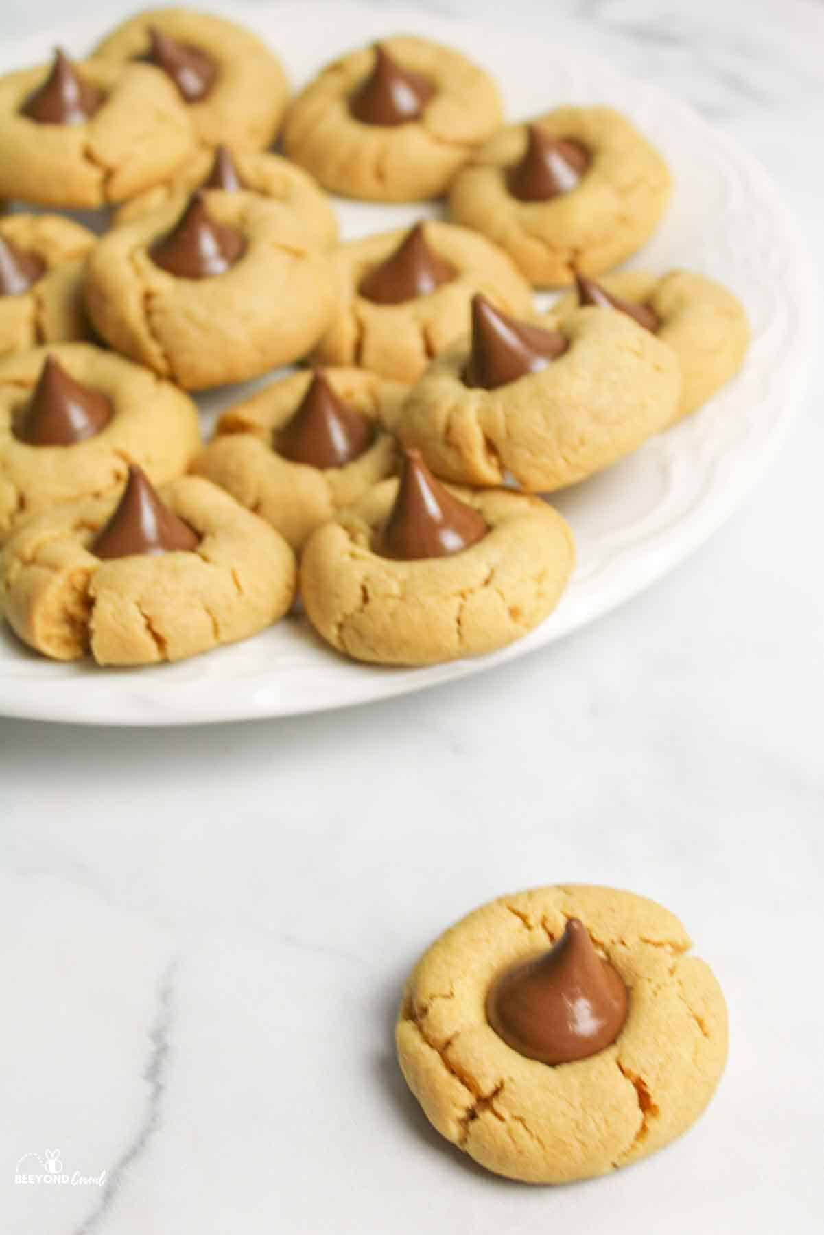 a plate of peanut butter blossom cookies with one off of the plate in front
