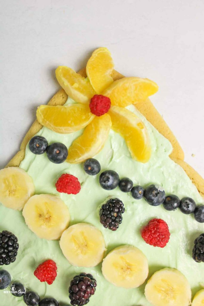 a close up of the orange peel and raspberry center star on christmas tree fruit pizza