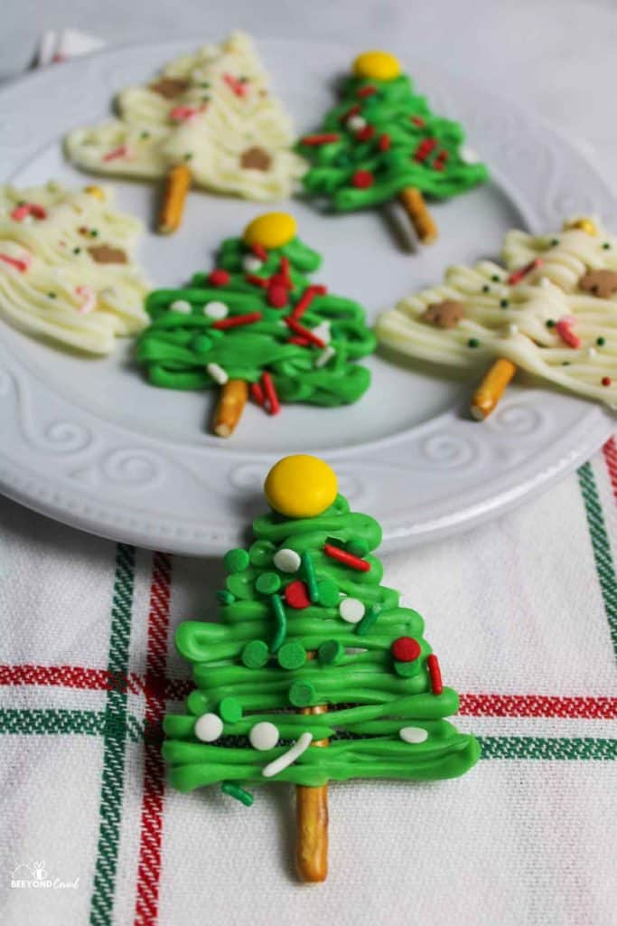 a plate of christmas tree pretzels with one resting off of the plate