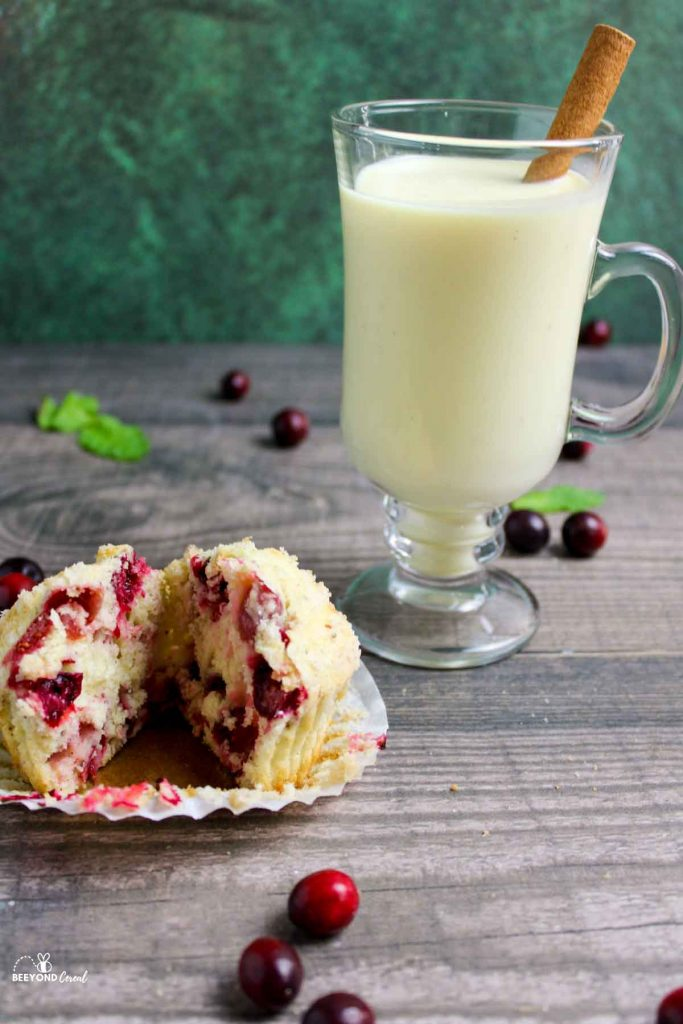 cranberry eggnog muffin split open next to glass of eggnog