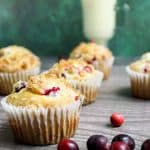 side view of cranberry eggnog muffins with fresh cranberries scattered around