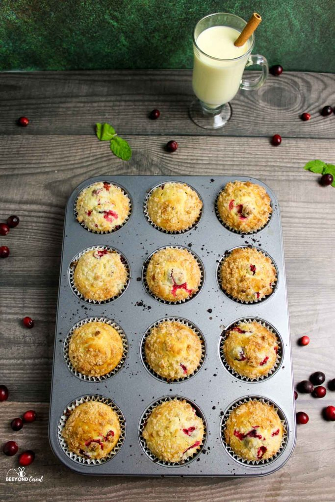 aerial view of tray of cranberry eggnog muffins next to glass of eggnog