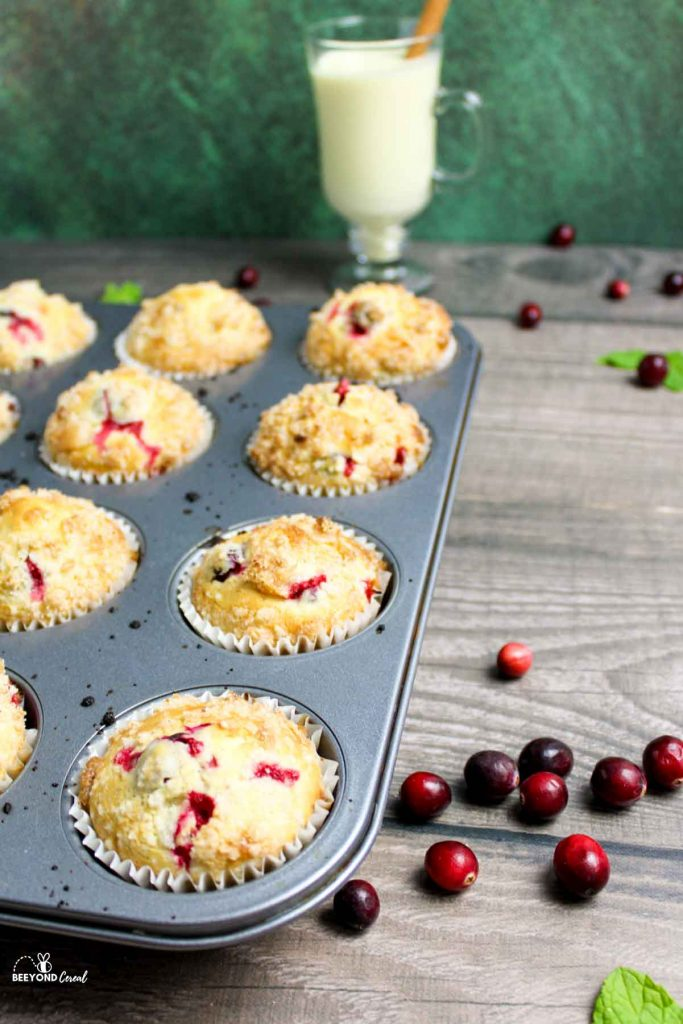 side angled view of a muffin tray full of cranberry eggnog muffins