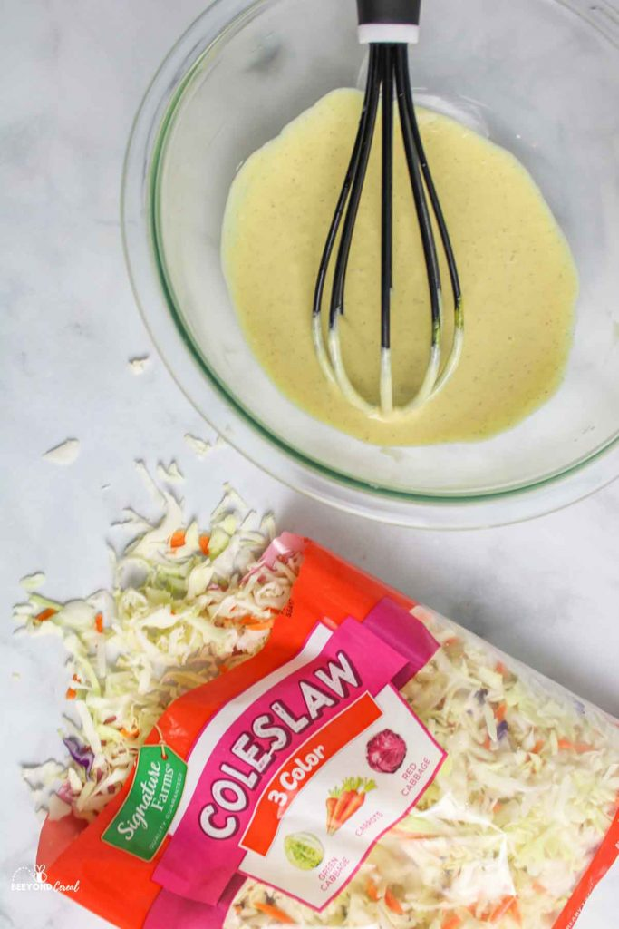 mixed coleslaw dressing and whisk next to bag of coleslaw