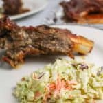 Dairy free coleslaw next to rib on white plate