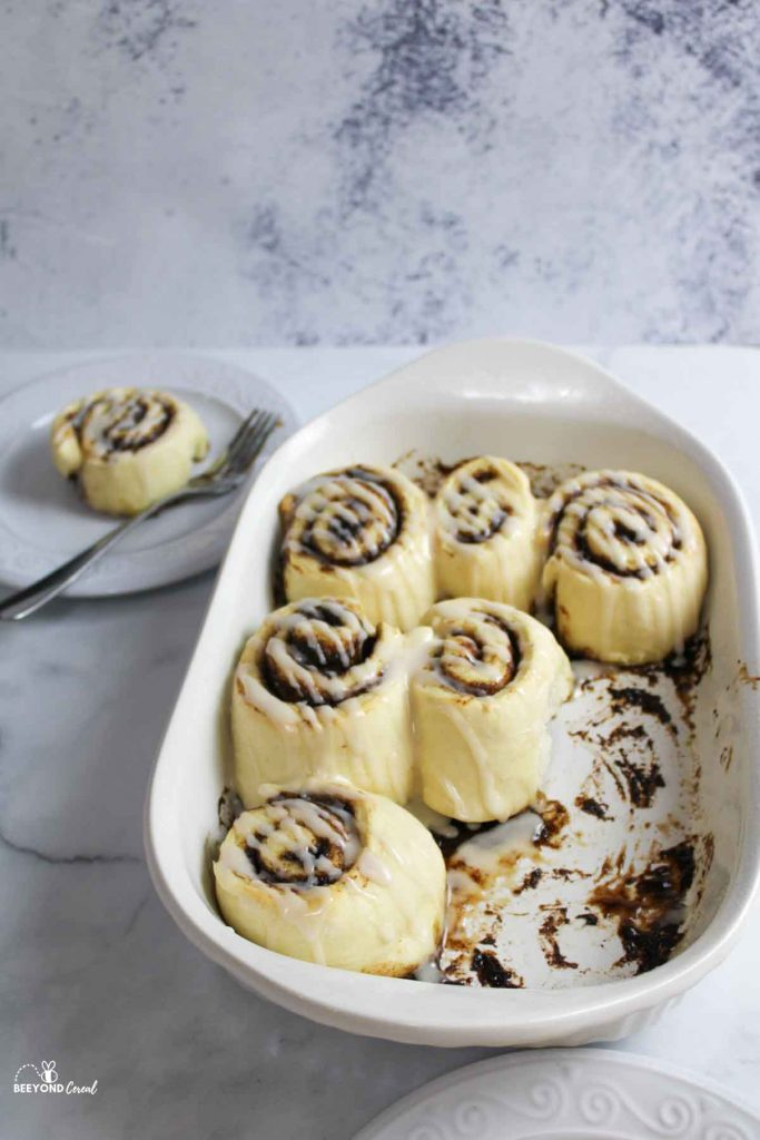 a baking dish with cinnamon rolls with some gone and one on a plate in back