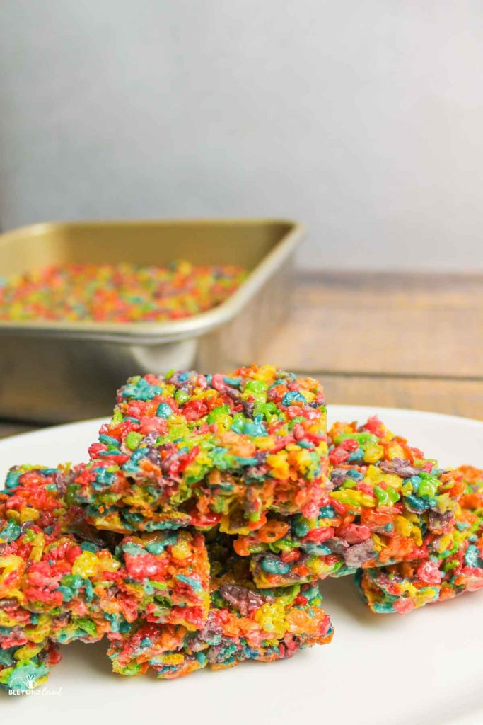 close up of stacked fruity pebbles treats on platter with more in background