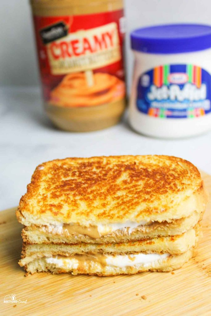 sliced and stacked halves of a grilled flutternutter in front of jars of peanut butter and fluff