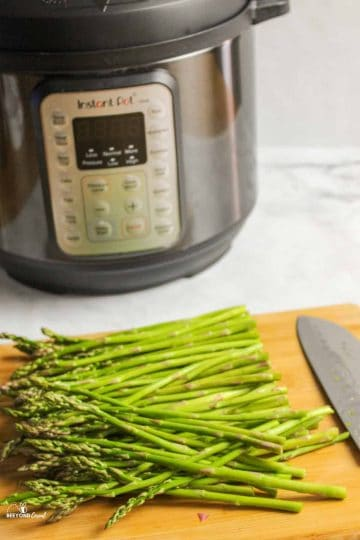 sliced asparagus on wooden board in front of instant pot