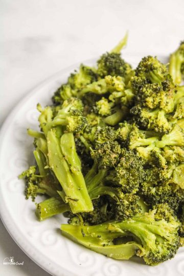a pile of seasoned and steamed broccoli on white plate