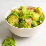 a bowl of cooked brussel sprouts with a brussel leaf on the side