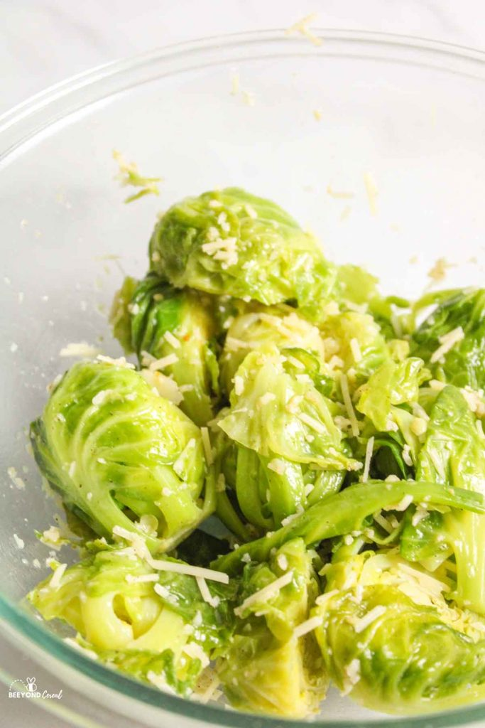 seasoned and cheese covered steamed brussel sprouts in glass bowl