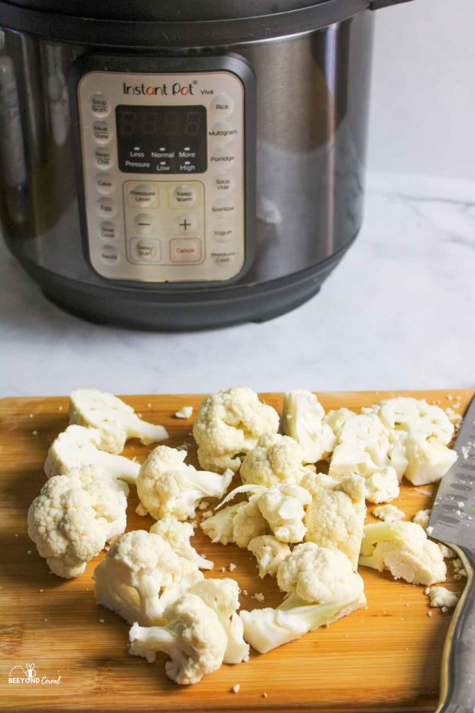 sliced cauliflower on board in front of instant pot
