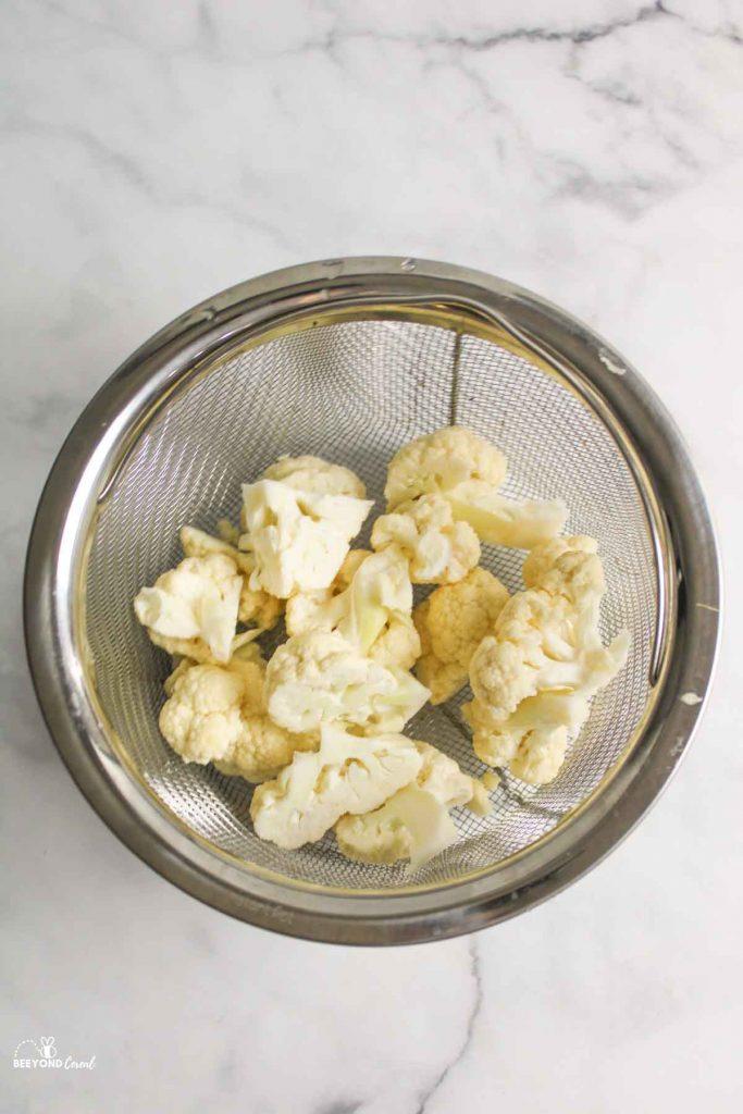aerial view of cauliflower in instant pot steamer basket