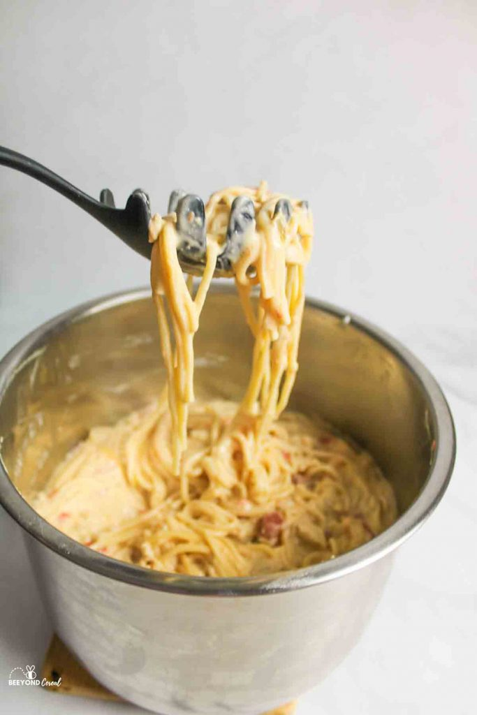 a pasta server holding up a scoop of instant pot chicken spaghetti above the stainless steel pot
