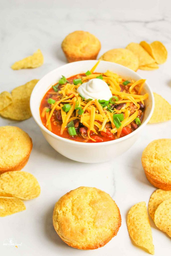 a bowl filled with chili surrounded by chips and corn muffins