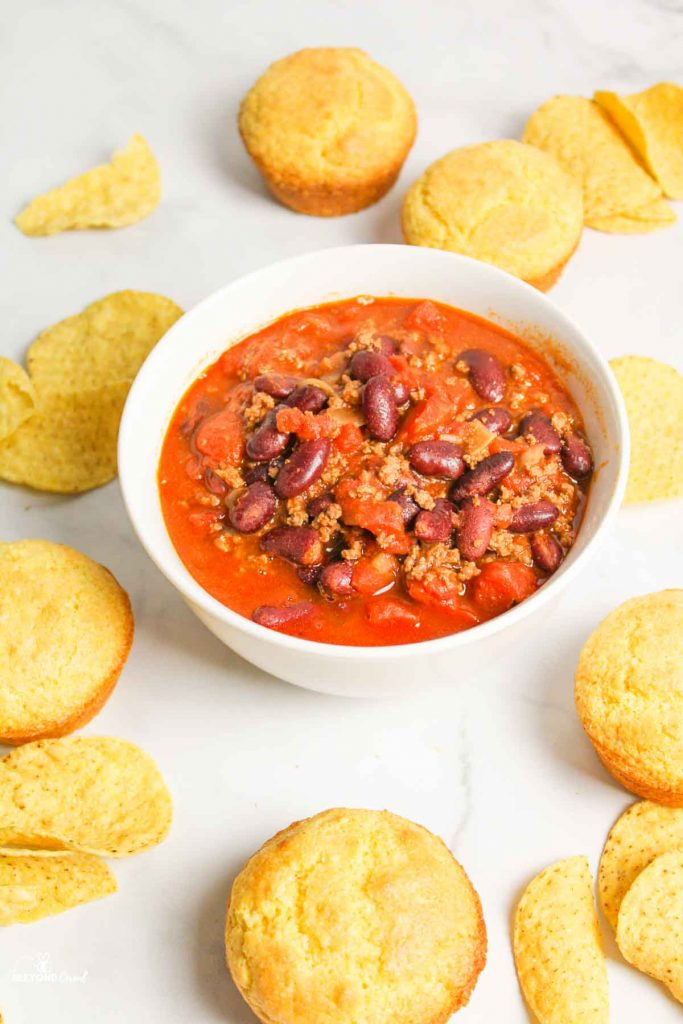 chili in a bowl with tortilla chips and corn muffins around it