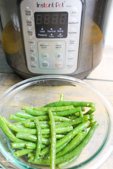 a glass bowl full of cooked green beans in front of instant pot