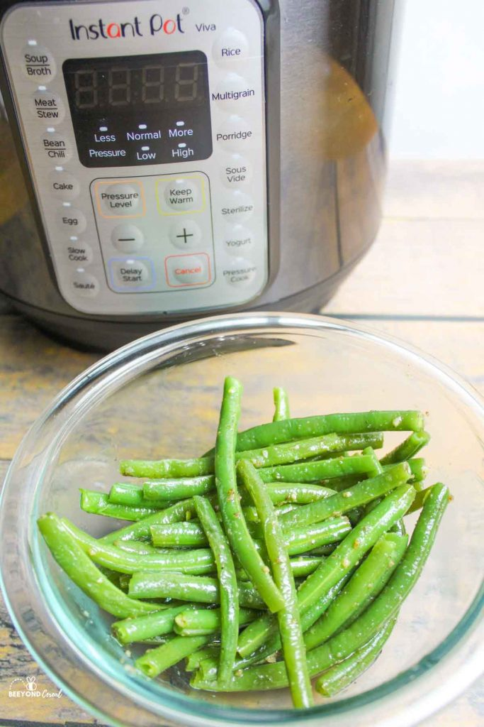 a bowl of seasoned cooked green beans in front of instant pot