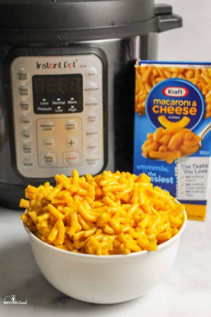 a white bowl filled with kraft mac in front of instant pot and box of kraft mac