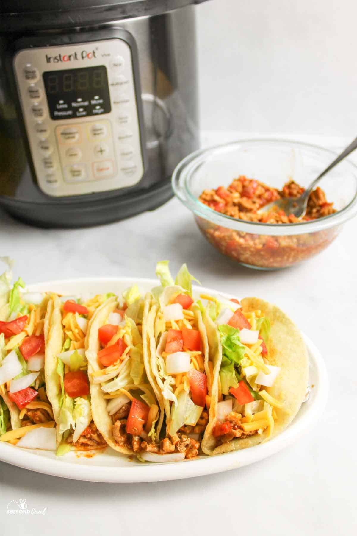 instant pot next to bowl of turkey taco meat and several turkey tacos with toppings