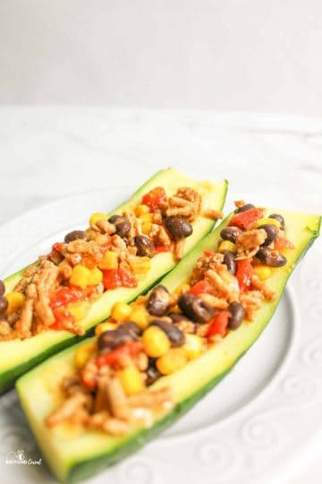 a plate with two zucchini boats on it