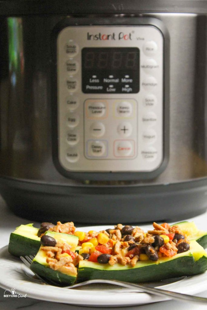 an upclose view of taco zucchini boat in front of instant pot