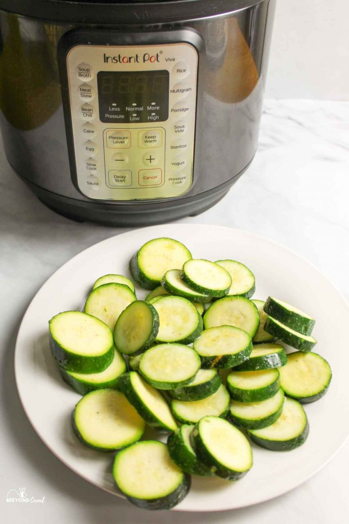 a plate of zucchini slices in front of instant pot