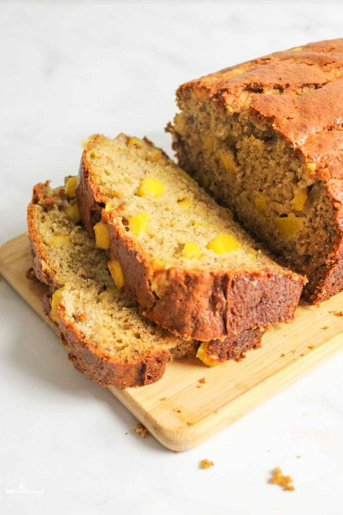 two slices of cut mango banana bread falling over on board