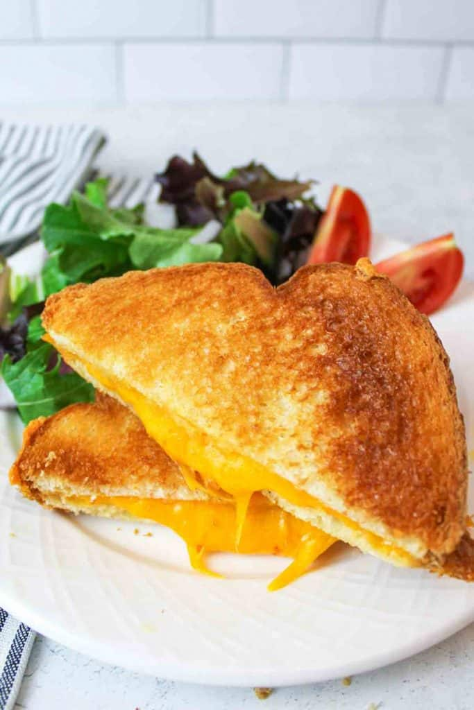 grilled cheese sandiwches on plates with melted cheese coming out the sides