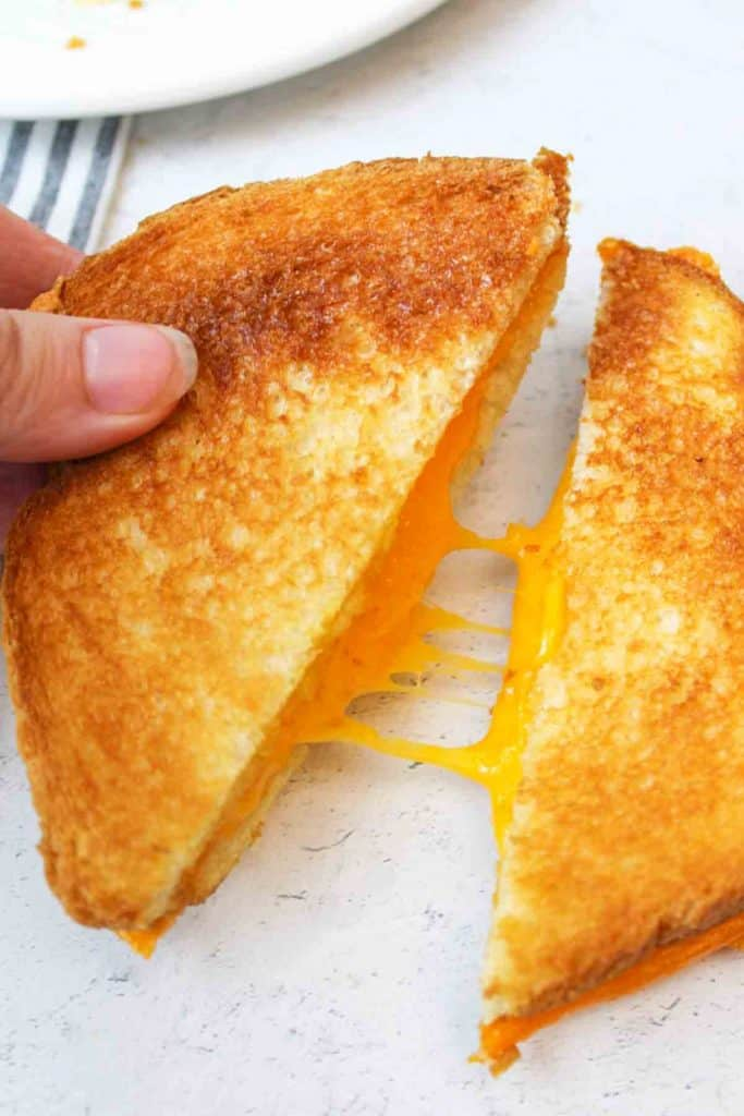 an upclose view of melted cheese coming out of a grilled cheese