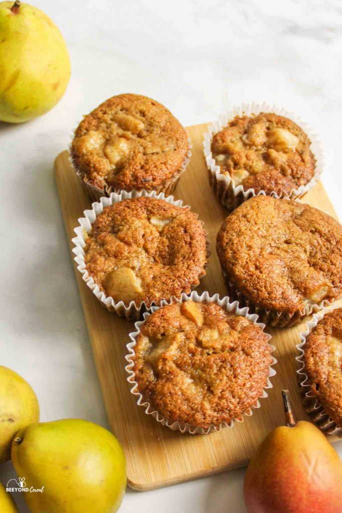 several pear muffins on wooden board surrounded by fresh pears