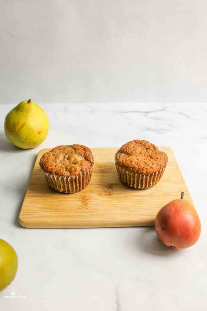 two pear muffins on a wooden board near fresh pears