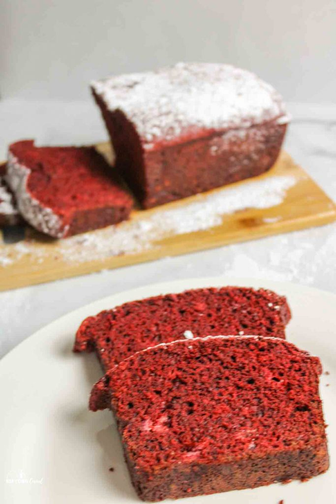 two slices of red velvet banana bread on a plate with loaf in background