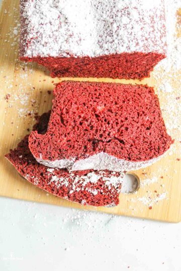two slices of red velvet banana bread on a plate with a sliced loaf in back