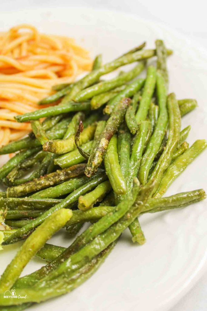 a side of roasted green beans next to spaghetti