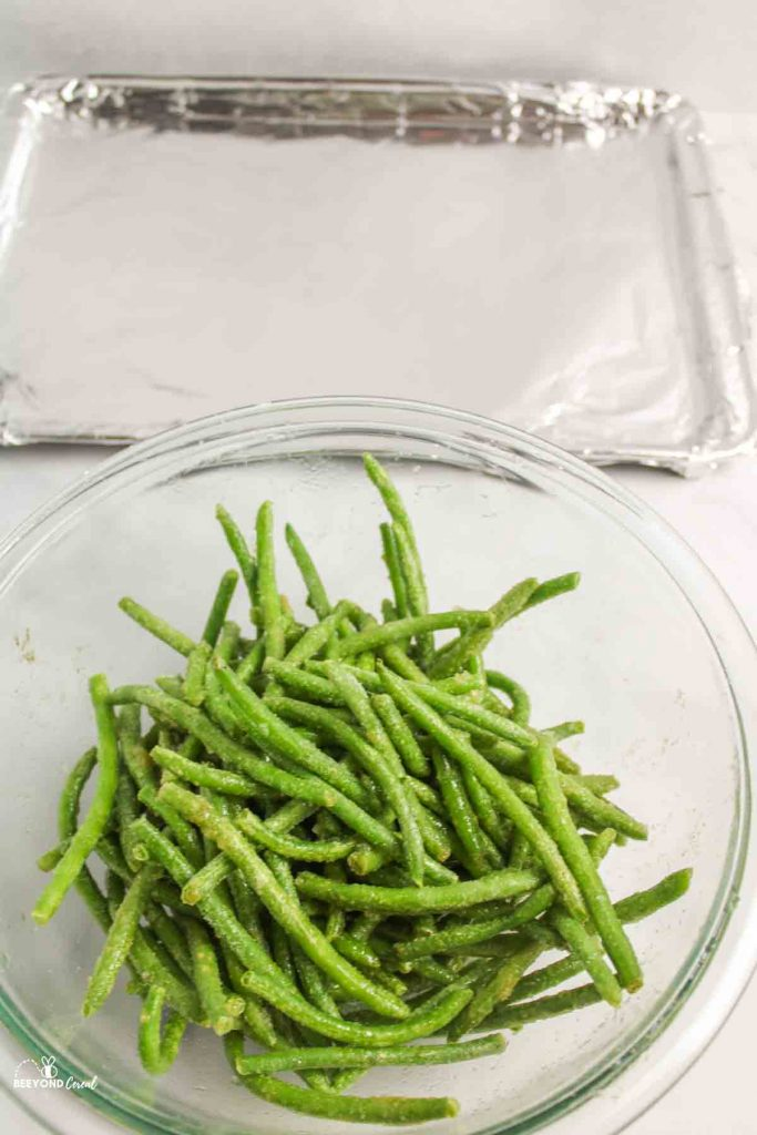 bowl of seasonings and frozen green beans in front of foil lined pan