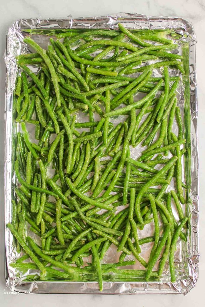 forozen seasoned green beans on foil lined pan ready for roasting
