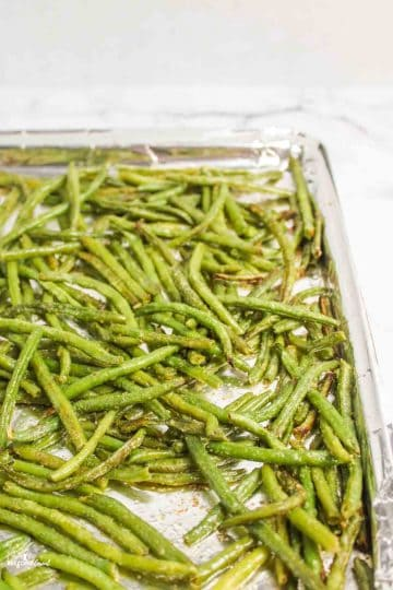 corner of a foil lined pan filled with roasted green beans