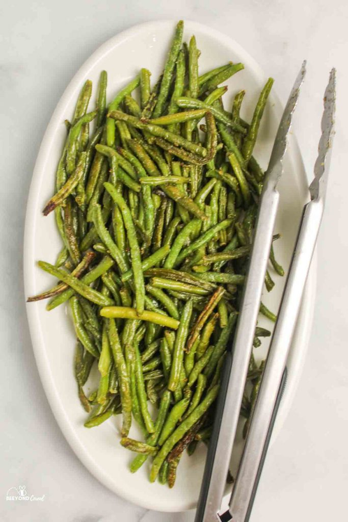 aerial view of white oval platter wth roasted green beans and a metal pair of tongs