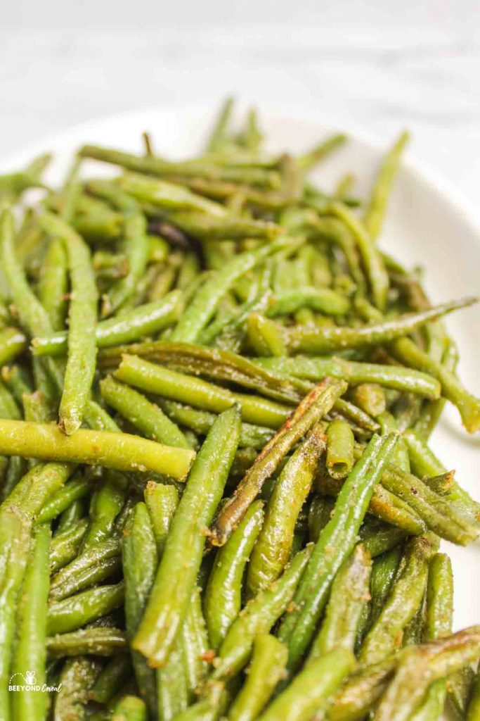 close side view of roasted green beans on plate