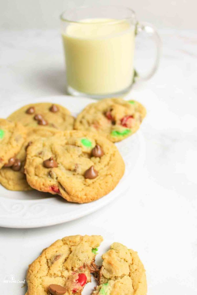 plate of chocolate chip m&m cookies with one broken off to the bottom of the picture and a cup of milk in the background