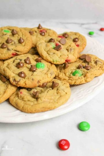 side view of a plate full of chocolate chip m&m cookies