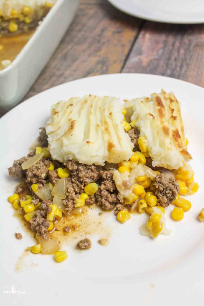 a serving of shepherds pie with corn on a white plate